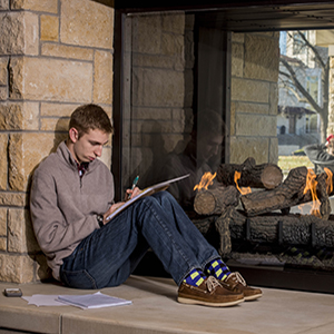 Student studying in front of fireplace