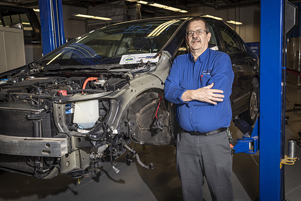 Eric Showalter stands next to a Recycled Rides car that was later donated