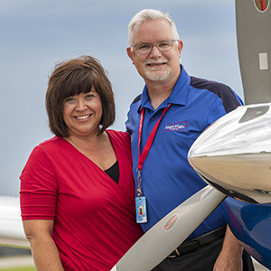 Kristi and Brendan Sneegas in front of an airplane at downtown Kansas City airport