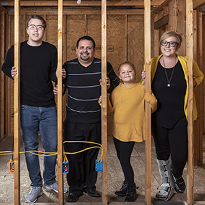 Janice Watkins and her family posing at a build site